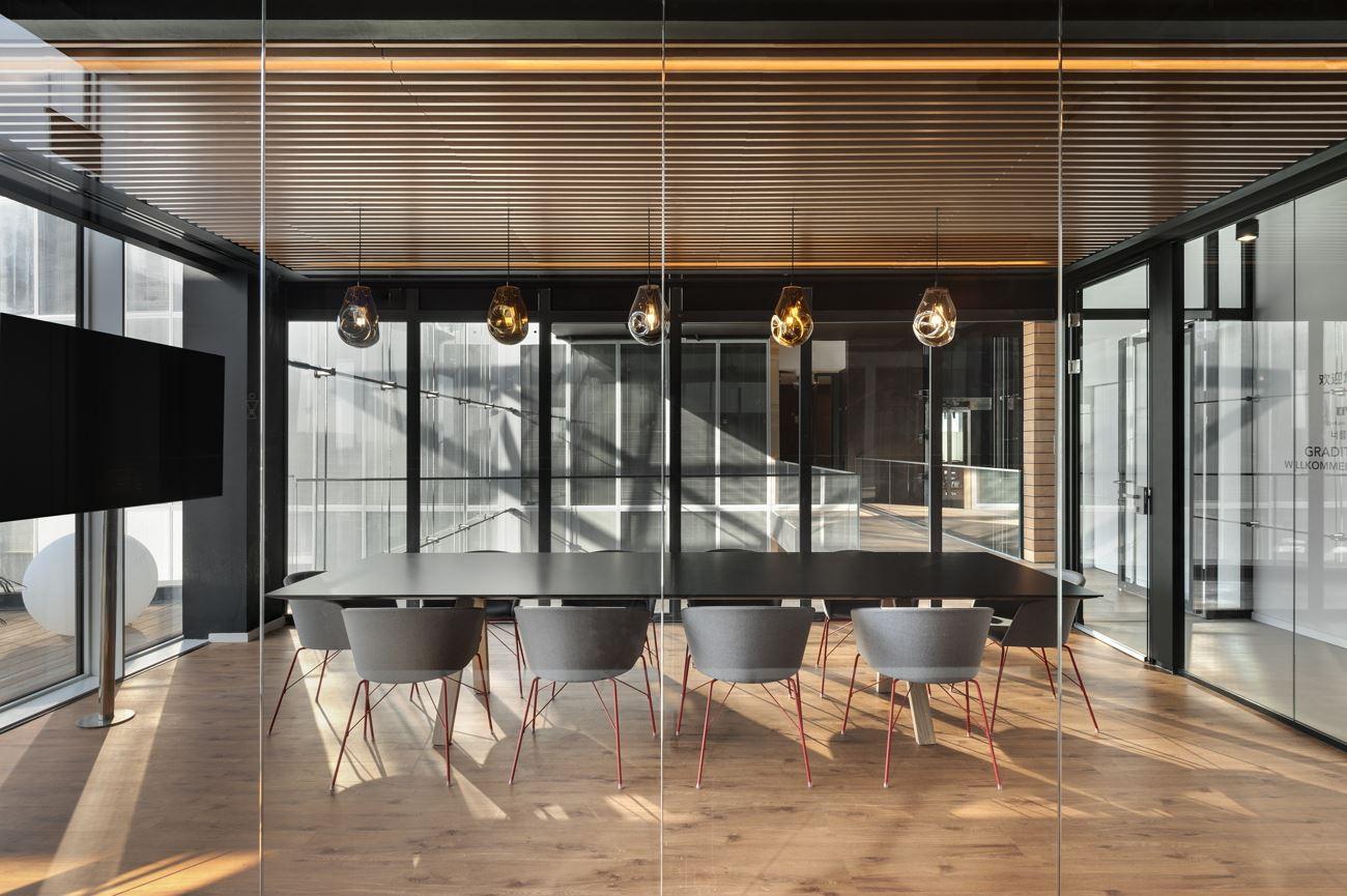 Innovation Offices מבט מחוץ לחדר על גוף תאורה מעל שולחן הישיבות בתכנון קמחי דורי