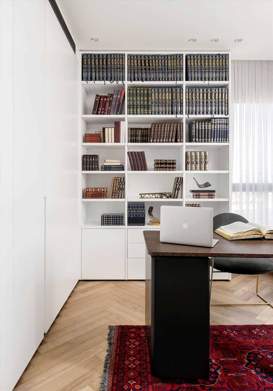 Penthouse - Petah Tikva גופי תאורה מאירים את הספרייה בחדר העבודה בתכנון דורי קמחי